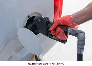 Mans hand wearing glove while pumping gas during the COVID-19 pandemic.