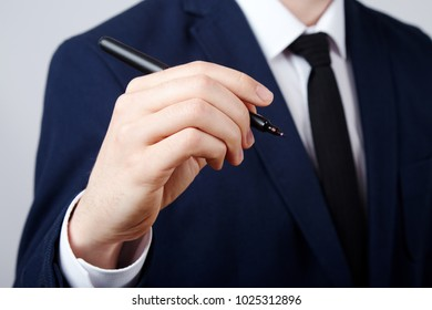 Man's hand wearing white shirt and suit at studio background, close up, business concept, holding a pen, writing.