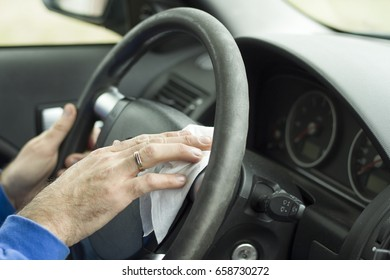 The man's hand wipes the steering wheel of the car with a white cloth.