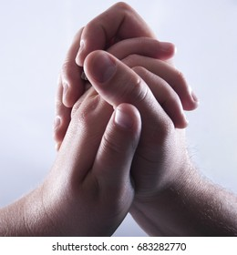 A mans hand and a woman's hand are clasped in love and connection.