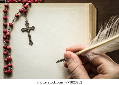 Man's hand writing a bible with old quill pen on the brown table in quiet, dark atmosphere. Rosary beads on the old page. Religion concept. Historical vintage style. Empty place for text.