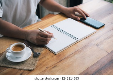 man's hand writing on paper with cup of coffee espresso.