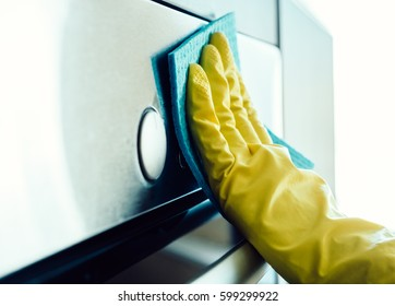 Man's hand in yellow glove cleaning the kitchen oven with rag
