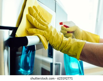 Man's hand in yellow rubber glove with rag cleaning kitchen oven