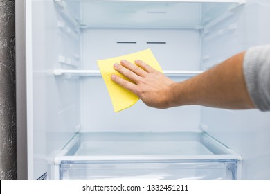 man's hand in yellow rubber protective glove cleaning white open empty refrigerator with green rag