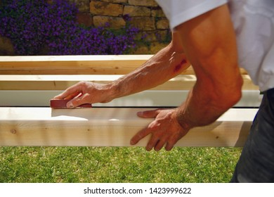 man's hands and arms smoothing natural wooden beam using sandpaper while he is working outside. Sanding of wood beams spruce for carport. Profession, carpentry and woodwork concept.