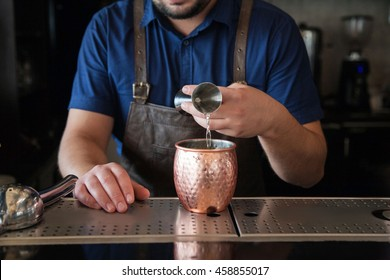 mans hands of  bartender poured from jigger to goblet