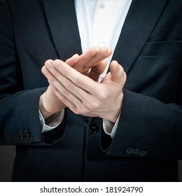 Man's hands clapping with a dark suit in the background.