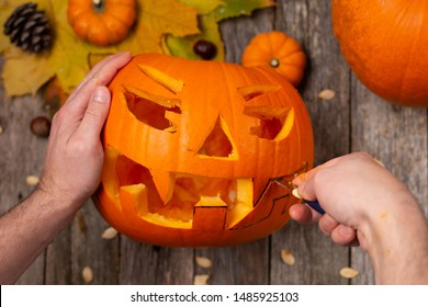 Man's hands close-up carve pumpkin for Halloween on wooden rustic table. Halloween autumn concept.