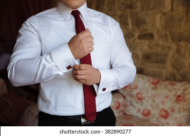 Mans hands with cufflinks. Gentleman in white shirt and red tie