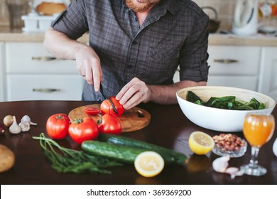 man's hands cut tomato on the board for a vegetarian salad