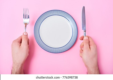 Man's hands with cutlery and empty plate isolated on green