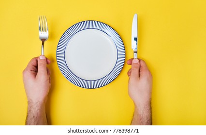 Man's hands with cutlery and empty plate isolated on yellow