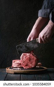 Man's hands cutting raw uncooked black angus beef tomahawk steaks on bones by vintage butcher cleaver on round wooden slate cutting board over dark wooden plank table. Rustic style