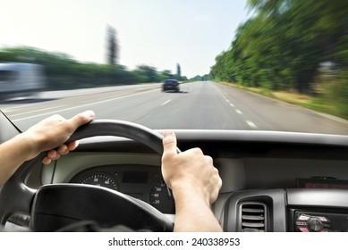 Man's hands of a driver on steering wheel of a minivan car on asphalt road