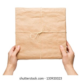 Man's hands gives parcel wrapped in brown paper and tied with rough twine
