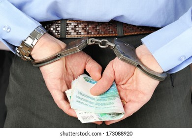 Man's hands in handcuffs and money in his palms