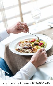 Man's hands with healthy vegetarian meal on table in restaurant.