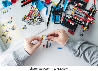 Man's hands hold plastic details of construction. Colourful bricks and manual on white table.