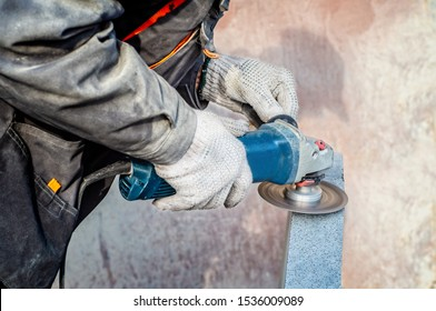 Man's hands holding angle grinder and grinding a stone. Close view.
