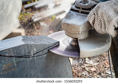 Man's hands holding angle grinder and cutting a stone. Close view.