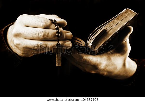 Man's hands holding bible and rosary during prayer - sepia toned on black background