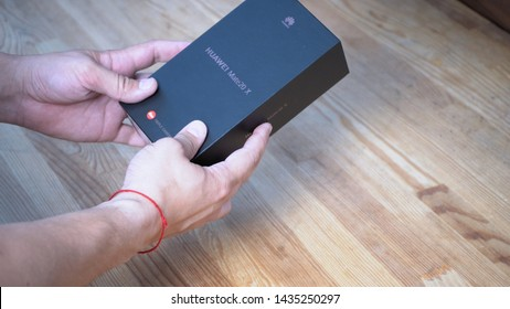 Mans hands holding black box with telephone inside on wooden background. He is showing logo of the company printed on the luxury package Kyiv, Ukraine 15th of June 2019