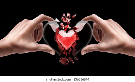 Man's hands holding broken heart isolated on black background