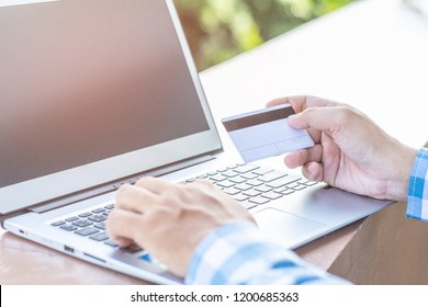 Man's hands holding a credit card and using laptop for online shopping.