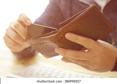 Man's hands holding a credit card in wallet and wireless computer keyboard , color filter image , business concept and idea