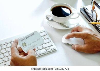 Man's hands holding a credit card and using computer for online shopping.