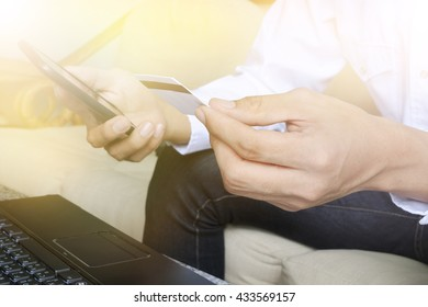 Man's hands holding a credit card  and wireless computer keyboard , color filter image ,,business shopping online