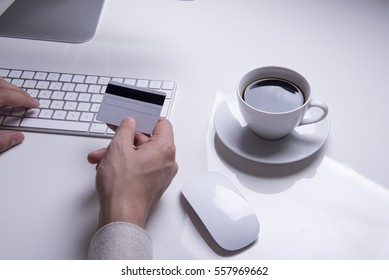 Man's hands holding a credit card for online shopping