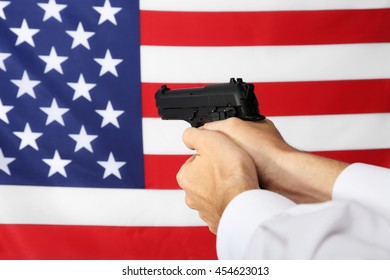 Man's hands holding gun on star and stripes background