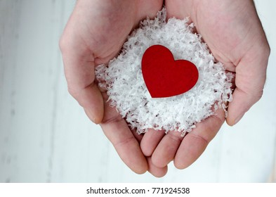mans hands holding heart in snow