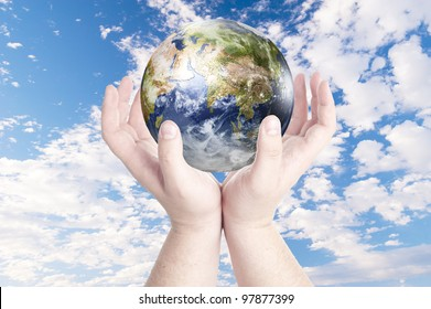 Man's hands holding on globe on cloudy blue sky. Concept for environmental protection from global warming. Data source: Nasa