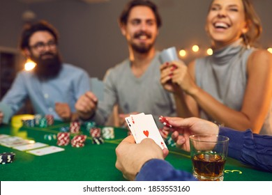 Mans hands holding playing cards with aces, poker chips and drink in glass during poker gambling over smiling friends faces at background, close-up, selective focus. Gambling, casino, poker concept
