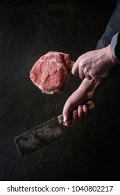 Man's hands holding raw uncooked black angus beef tomahawk steaks on bones and vintage butcher cleaver over dark background. Rustic style