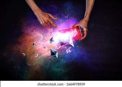 Man`s hands holding a small magic paper box with flying ethereum cymbols, mixed media . Mixed media