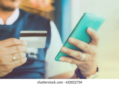 Man's hands holding smart phone using credit card for online shopping