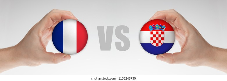 Man's hands holding styrofoam balls with flags of France and Croatia against the white background.