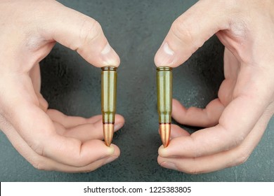 Man's hands are holding two 7.62 mm cartridges for a Kalashnikov assault rifle between fingers