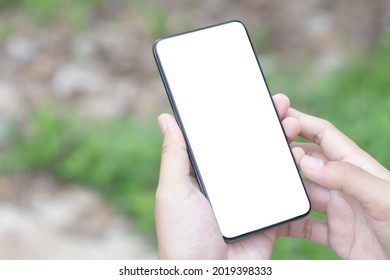 Man's hands holding or using smartphone with two hands. Smartphone with white blank on screen, Cellphone mockup.