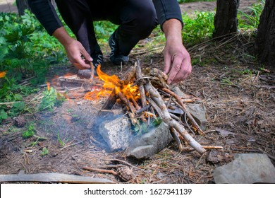 Man's hands making campfire in forest, the stones form a circle around the fire to protect nature. Man's hand throwing firewood for maintaining fire. Tourist man's hands kindle a fire in the mountains
