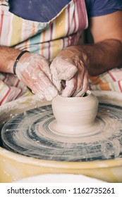 Man's hands making ceramic pot on the pottery wheel. Craftsman creating pottery working on the wheel shaping clay making vase. Close up.