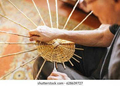 Man's hands making a wicker basket