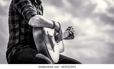 Man's hands playing acoustic guitar, close up. Acoustic guitars playing. Music concept. Black and white.