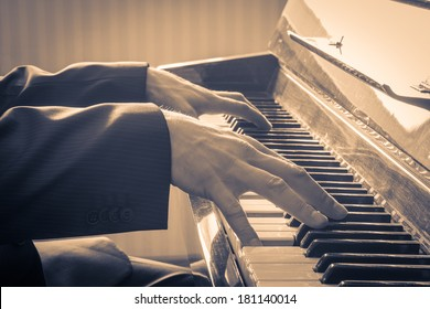 Man's hands playing the Piano.  Retro Style. Warm color toned