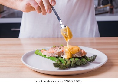 Man's hands pouring hollandaise sauce on top of delicious baked salmon with steamed green asparagus. Food presentation preparation process