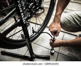 a man's hands pumping up a bike tire using small pump.